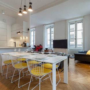 Cette image montre une salle à manger ouverte sur le salon design de taille moyenne avec un mur blanc et un sol en bois clair.