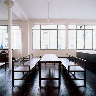 Réalisation d'une grande salle à manger ouverte sur le salon urbaine avec un mur blanc et un sol en bois foncé.