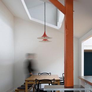 Cette image montre une salle à manger ouverte sur le salon design de taille moyenne avec un mur blanc.