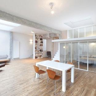 Idées déco pour une grande salle à manger ouverte sur le salon moderne avec un mur blanc et un sol en bois clair.