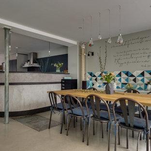 Aménagement d'une salle à manger ouverte sur la cuisine industrielle avec un mur gris, béton au sol et un sol gris.