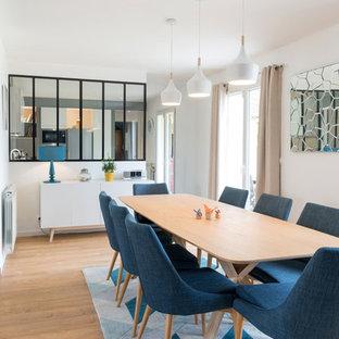Réalisation d'une grand salle à manger ouverte sur le salon design avec un mur blanc, aucune cheminée, un sol en bois clair et un sol beige.