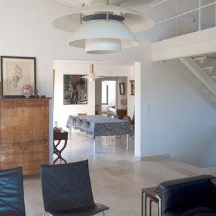 Idee per una sala da pranzo aperta verso il soggiorno tradizionale di medie dimensioni con pareti bianche, pavimento in travertino, stufa a legna, cornice del camino in metallo e pavimento beige