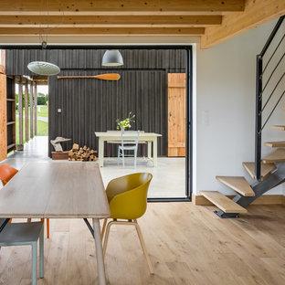 Idées déco pour une salle à manger industrielle de taille moyenne avec un mur blanc, un sol en bois brun et un sol marron.