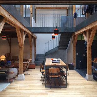 Idée de décoration pour une salle à manger ouverte sur le salon chalet de taille moyenne avec un mur blanc, un sol en bois brun et un sol beige.