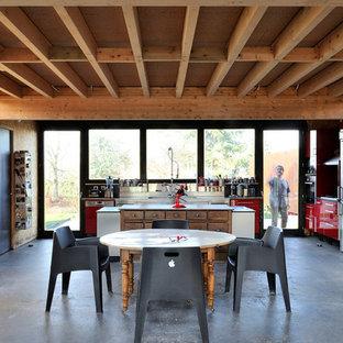 Idées déco pour une grande salle à manger ouverte sur le salon industrielle avec un mur marron et béton au sol.