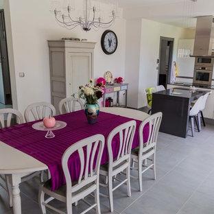 Exemple d'une grande salle à manger ouverte sur le salon moderne avec un mur blanc et un sol gris.