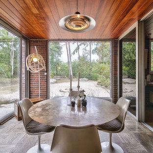 Exemple d'une salle à manger rétro fermée avec aucune cheminée et un sol marron.