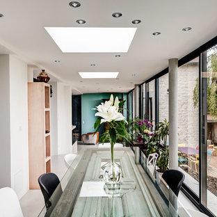 Idée de décoration pour une très grande salle à manger design fermée avec un mur blanc, béton au sol et aucune cheminée.