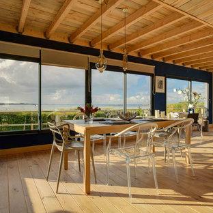 Idées déco pour une salle à manger bord de mer avec un mur bleu, un sol en bois brun et un sol marron.