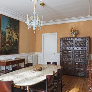 Cette image montre une salle à manger traditionnelle fermée et de taille moyenne avec un mur orange, un sol en bois brun, une cheminée standard et un manteau de cheminée en pierre.