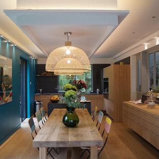 Idée de décoration pour une salle à manger ouverte sur la cuisine design de taille moyenne avec un mur bleu, un sol en bois clair et aucune cheminée.