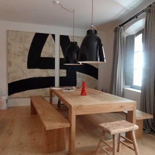 Exemple d'une salle à manger tendance fermée et de taille moyenne avec un mur blanc et un sol en bois clair.