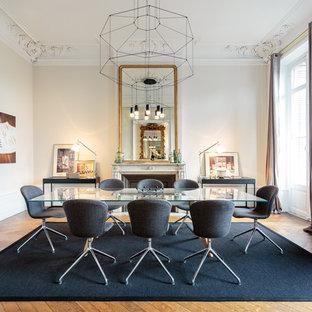 Cette image montre une salle à manger design avec un mur beige, un sol en bois brun et une cheminée standard.