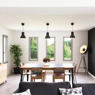 Aménagement d'une salle à manger ouverte sur le salon industrielle avec un mur blanc, aucune cheminée et un sol gris.