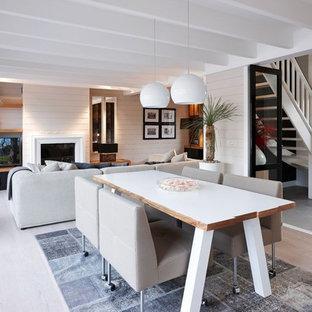 Idée de décoration pour une salle à manger ouverte sur le salon tradition de taille moyenne avec un mur gris et un sol en bois clair.