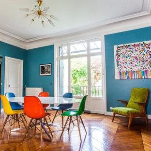 Aménagement d'une grand salle à manger contemporaine fermée avec un mur bleu et un sol en bois brun.