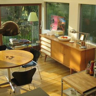 Inspiration pour une salle à manger ouverte sur le salon nordique de taille moyenne avec un mur blanc, un sol en bois clair, une cheminée standard, un manteau de cheminée en plâtre et un sol marron.