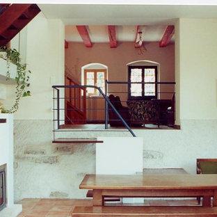 Imagen de comedor de estilo de casa de campo, de tamaño medio, cerrado, con paredes blancas, suelo de baldosas de cerámica, chimenea de doble cara, marco de chimenea de hormigón y suelo naranja
