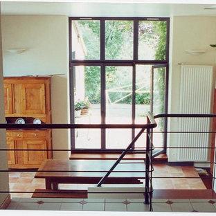 Idées déco pour une salle à manger campagne fermée et de taille moyenne avec un mur blanc, un sol en carrelage de céramique, une cheminée double-face, un manteau de cheminée en béton et un sol orange.