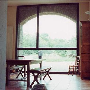 Foto de comedor campestre, de tamaño medio, cerrado, con paredes blancas, suelo de baldosas de cerámica, chimenea de doble cara, marco de chimenea de hormigón y suelo naranja