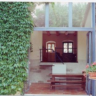 Diseño de comedor campestre, de tamaño medio, cerrado, con paredes blancas, suelo de baldosas de cerámica, chimenea de doble cara, marco de chimenea de hormigón y suelo naranja