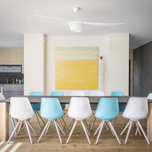 Exemple d'une salle à manger ouverte sur la cuisine tendance avec un mur multicolore et un sol en bois clair.