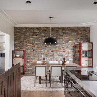Cette image montre une salle à manger ouverte sur la cuisine design de taille moyenne avec un mur multicolore, un sol en bois brun, aucune cheminée et un sol marron.