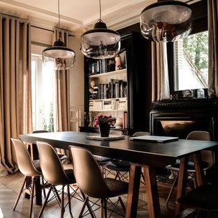 Idées déco pour une salle à manger ouverte sur le salon contemporaine de taille moyenne avec un sol en bois foncé, une cheminée standard et un mur noir.