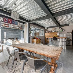 Cette photo montre une grande salle à manger ouverte sur le salon industrielle avec un mur gris et béton au sol.