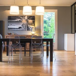 Cette image montre une salle à manger ouverte sur le salon design avec un mur gris et un sol en bois brun.
