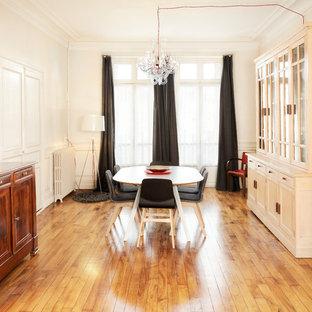 Aménagement d'une grande salle à manger classique fermée avec un mur beige, un sol en bois brun, un sol beige, une cheminée standard et un manteau de cheminée en pierre.