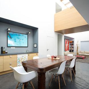 Idées déco pour une grand salle à manger ouverte sur le salon contemporaine avec un mur blanc, béton au sol, aucune cheminée et un sol noir.