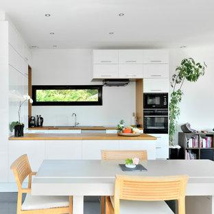 Cette photo montre une salle à manger ouverte sur la cuisine tendance avec un mur blanc et béton au sol.