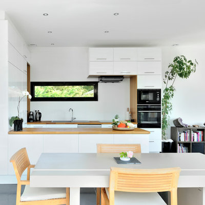 Inspiration for a contemporary concrete floor kitchen/dining room combo remodel in Lyon with white walls
