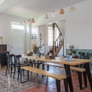 Idée de décoration pour une salle à manger champêtre avec un mur blanc et un sol rouge.