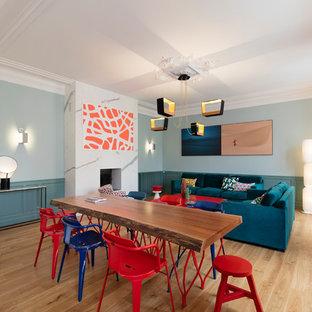 Exemple d'une salle à manger tendance avec un mur bleu, un sol en bois clair et une cheminée standard.