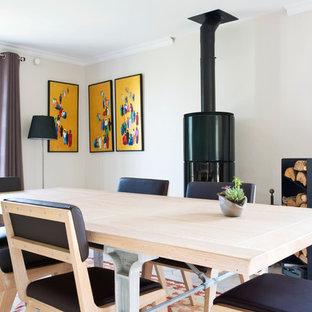 Cette image montre une salle à manger rustique fermée avec un mur beige et un poêle à bois.