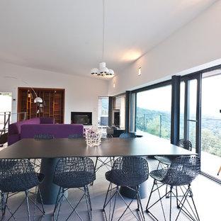 Aménagement d'une grand salle à manger ouverte sur le salon contemporaine avec un mur blanc, béton au sol et aucune cheminée.