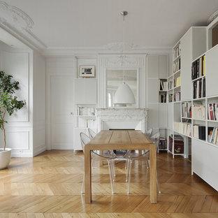 Idées déco pour une grande salle à manger classique fermée avec un mur blanc, un sol en bois clair, une cheminée standard et un manteau de cheminée en pierre.