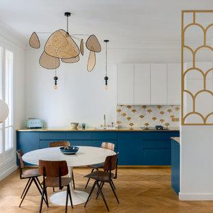 Cette photo montre une salle à manger ouverte sur la cuisine scandinave avec un mur blanc, un sol en bois brun et un sol marron.