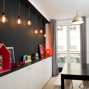 Inspiration for a mid-sized scandinavian light wood floor and brown floor dining room remodel in Paris with black walls and no fireplace