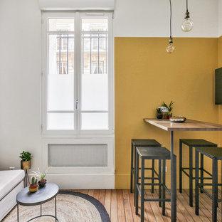 Foto di una sala da pranzo aperta verso il soggiorno industriale di medie dimensioni con pareti gialle, pavimento in legno massello medio, nessun camino e pavimento marrone