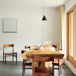 Réalisation d'une salle à manger ouverte sur la cuisine chalet avec un mur blanc et un sol noir.