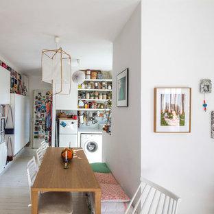Cette photo montre une salle à manger ouverte sur le salon tendance de taille moyenne avec un mur blanc, un sol en bois peint et aucune cheminée.