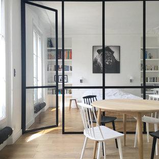 Immagine di una sala da pranzo scandinava di medie dimensioni con pareti bianche, parquet chiaro e nessun camino