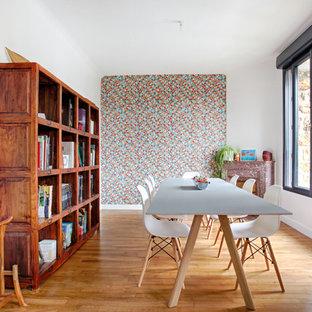 Exemple d'une salle à manger tendance fermée et de taille moyenne avec un mur orange, une cheminée standard, un manteau de cheminée en pierre et un sol en bois brun.