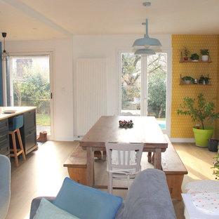 Idee per una sala da pranzo aperta verso il soggiorno scandinava con pareti gialle, pavimento in laminato e pavimento beige