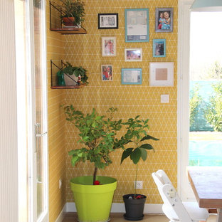 Foto di una sala da pranzo aperta verso il soggiorno scandinava con pareti gialle, pavimento in laminato e pavimento beige