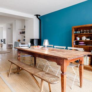 Cette photo montre une salle à manger ouverte sur le salon éclectique avec un sol en bois clair, un mur bleu et un poêle à bois.